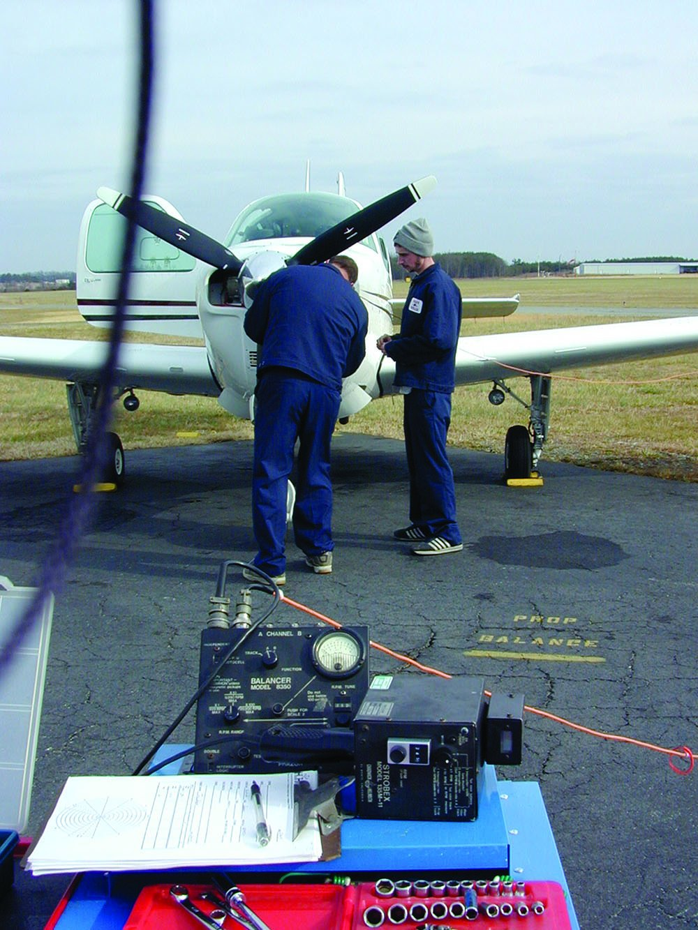 men balancing an aircraft propeller